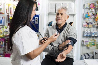 Female Chemist Checking Blood Pressure Of Senior Man