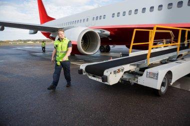 Worker Walking By Conveyor Truck With Airplane On Runway