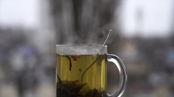 cup of hot tea on the daylight snowy cityscape background in slow motion