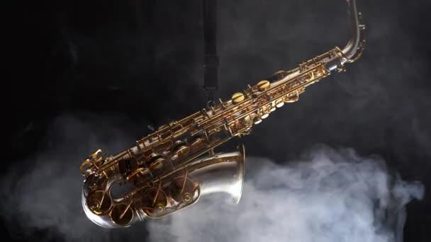 Arany fényes alto szaxofon lassan mozog a fekete háttérben a füst