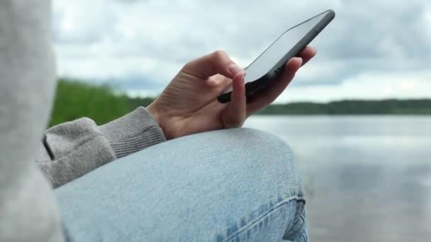 Zavřít ruce držení a používání mobilního chytrého telefonu venkovní.