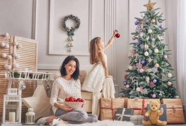 Mom and daughter decorate the Christmas tree.