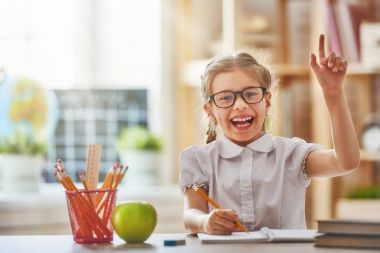 Back to school! Happy cute industrious child is sitting at a desk indoors. Kid is learning in class. stock vector