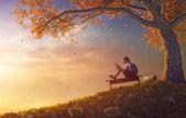 dítě čtení knihy poblíž stromu