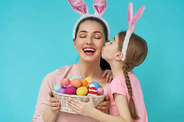 Happy holiday! Mother and her daughter with painting eggs. Family preparing for Easter. Cute little child girl is wearing bunny ears. stock vector