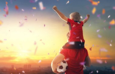 Cute little child dreaming of becoming a soccer player. Boy with man playing football on sunset. Family sport.