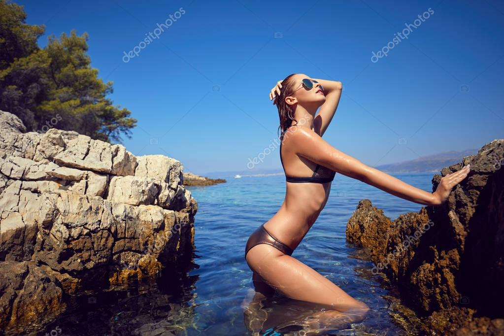 Pretty beautiful woman in swimwear bikini posing in blue sea water