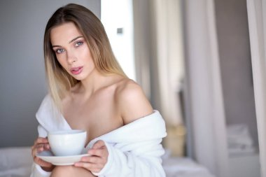 Enjoying morning coffee. Close-up of beautiful young woman holdi