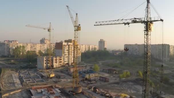 průmyslové stavební jeřáby a budování siluety nad slunce při východu slunce