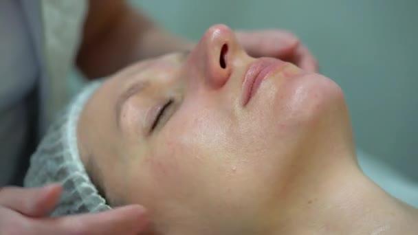Facendo un massaggio al viso a donna estetista