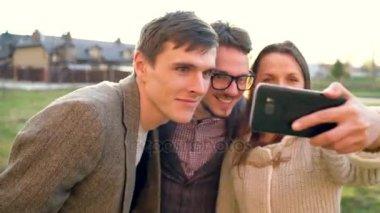 Smiling friends making selfie outdoors