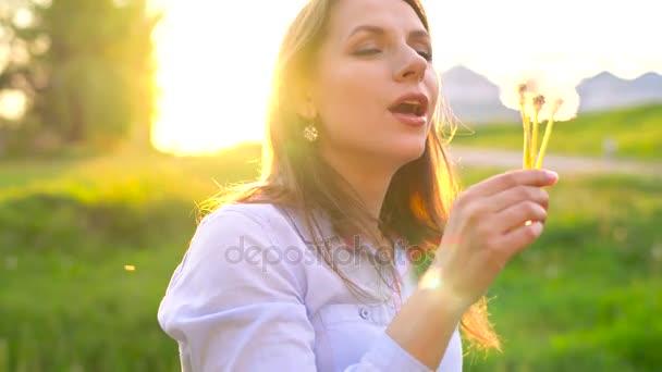 Krása žena fouká Pampeliška proti západu slunce