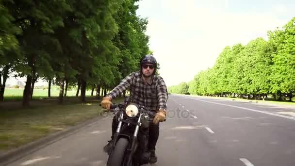 Motorkářská jízda na motorce na silnici obklopené stromy