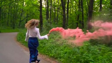 Woman in beautiful clothes runs through the forest waving colored smoke, slow motion