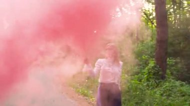 Woman in beautiful clothes runs through the forest waving colored smoke