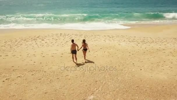 Happy couple carefree running to the water on the beach. Picturesque ocean coast of Portugal