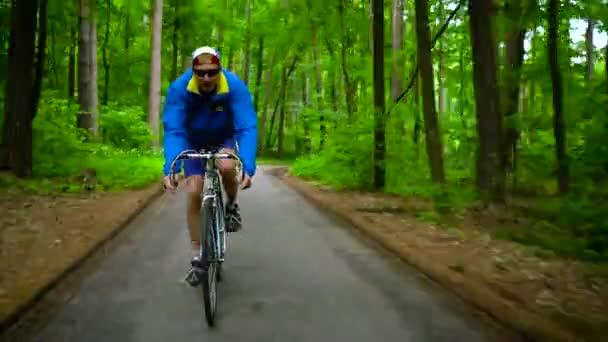 Muž středního věku je jízda silničním kole po lesní cestě