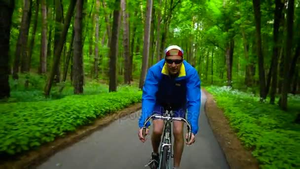 Muž středního věku je jízda silničním kole po lesní cestě, zpomalené