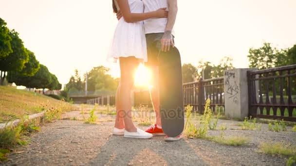 Fiatal pár szerelmes csók az utcán, a naplemente