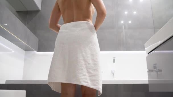 Žena vstupující do sprchy a klesá její ručník
