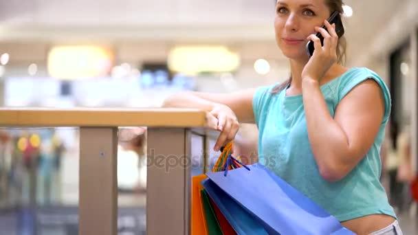 Nő beszél egy okostelefon, egy bevásárló központban papírzacskó