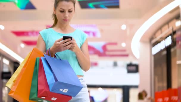 Woman with paper bags using smartphone in a shopping center
