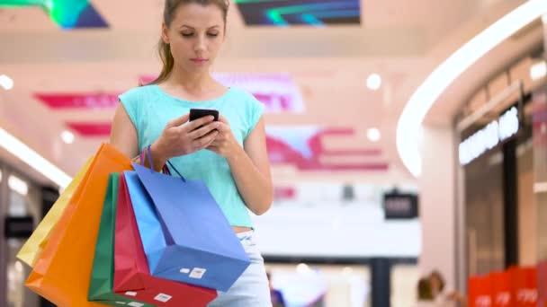 Žena s papírové tašky pomocí smartphone v nákupním centru