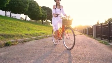 Young beautiful woman riding a bicycle at sunset. Video taken at different speeds