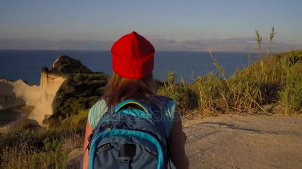 Woman with a backpack and map goes to the Cape Drastis at Corfu island in Greece