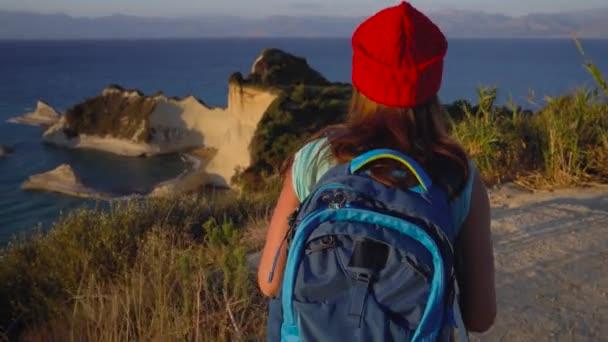 Frau mit einem Rucksack macht Foto von Kap Drastis auf Korfu in Griechenland