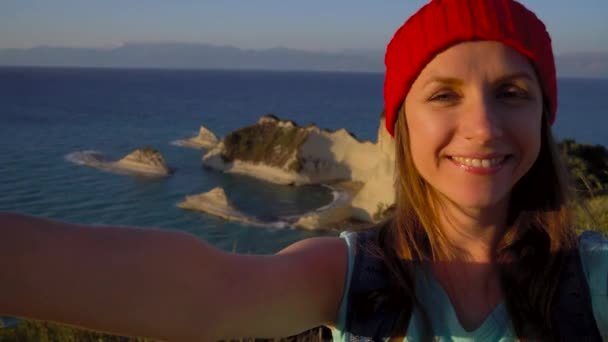 Frau mit einem Rucksack macht Selfie auf dem Hintergrund der Kap Drastis auf Korfu in Griechenland