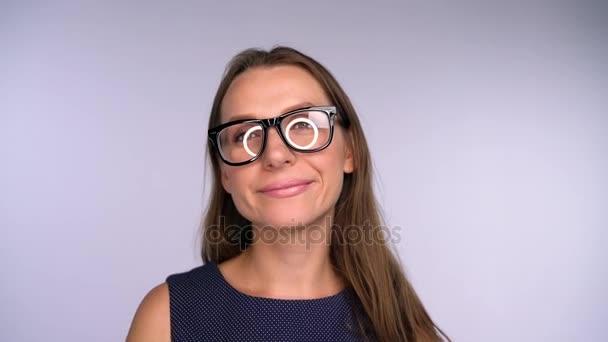 Mladá podnikatelka v brýlích při pohledu na fotoaparát šťastný. KRUHOVÁ záře se odráží v brýle