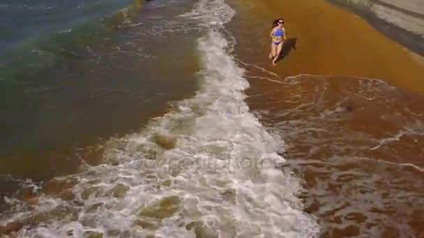 Beach bikini woman carefree running along the water on the beach. Picturesque sea coast of Corfu, Greece