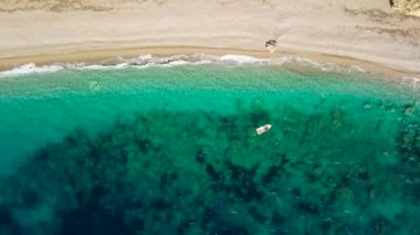 Aerial view of a boat in front of the Corfu island in Greece. Amazing beach with a turquoise and transparent sea