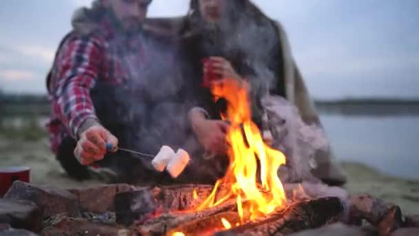 Liebespaar am Lagerfeuer am See sitzen, reden, trinken heißen Tee und Braten marshmallows
