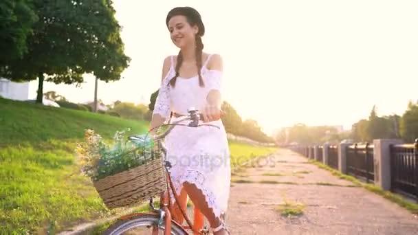 Mladá krásná žena, jízda na kole při západu slunce