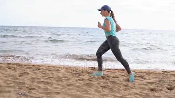 Sportovní žena pobíhající po pláži. Zpomalený pohyb