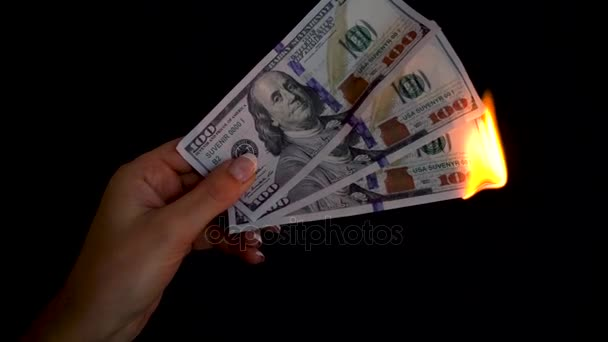 Burning dollars in a hand close-up on a black background