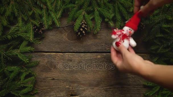 Dámské ruce vytvořit vánoční výzdoba. Vánoční stromek větve s kužely a vánoční ozdoby na dřevěné textury připravené pro návrh