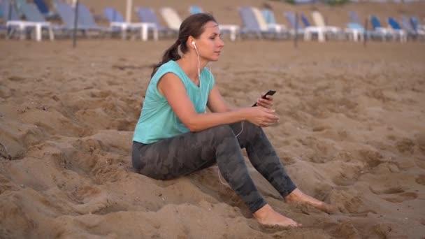Sportovní žena se sluchátky na uších sedí na pláži a odpočívá po běhání. Video při různých rychlostech - normální a pomalu