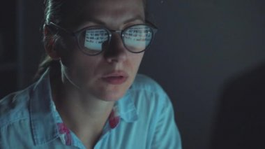 Woman in glasses looking on the monitor and surfing Internet