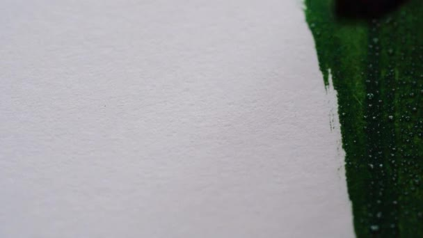 Zeichnen mit einem Pinsel auf weißem Papier mit grünen Aquarell Close up