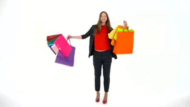 Female shopper holding multicolored shopping bags on white background in studio. Lets go shopping concept