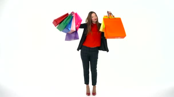Női shopper gazdaság tarka bevásárló táskák, fehér háttér a stúdióban. Menjünk bevásárlás koncepció