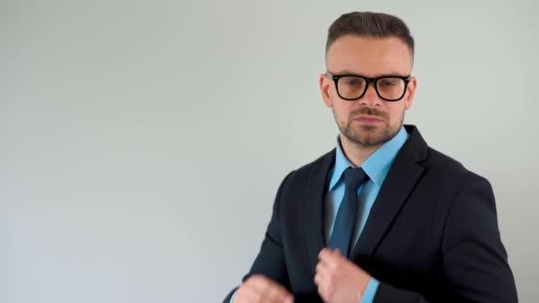 Portrét formálně oblečeného vousatého muže s brýlemi narovná kravatu a podívá se do kamery