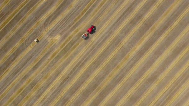 Letecký pohled na haytavu zpracovaný na kulaté baleny. Červený traktor pracuje v terénu.