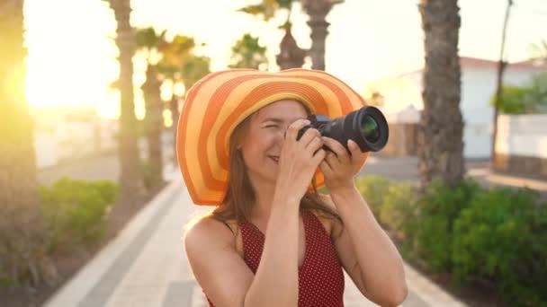 Fotografka turistické ženy ve velkém žlutém klobouku fotografovat s fotoaparátem v nádherné tropické krajině při západu slunce