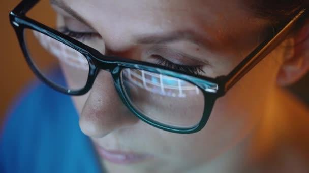 Žena v brýlích, při pohledu na monitor a procházení Internetu. Obrazovka monitoru se odráží v brýle
