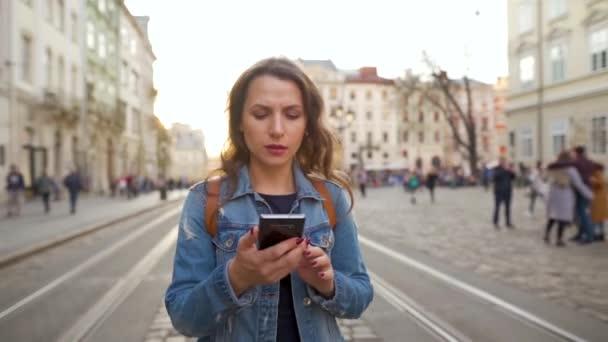 Mladá žena kráčí po staré ulici pomocí chytrého telefonu a velmi emocionálně reaguje na to, co tam vidí