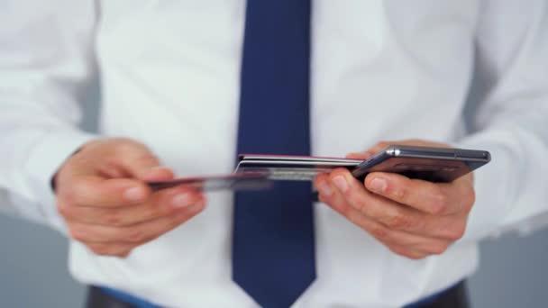 Formálisan öltözött férfi kiválaszt egy hitelkártyát több, és belép ez a szám egy okostelefon fizetni online. Online vásárlás, életmód technológia. Közelkép
